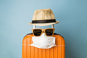 istock Suitcase with hat, sunglasses and protective medical mask on pastel blue background minimal creative coronavirus covid-19 travel concept. 1218246658