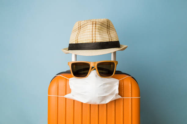 suitcase with hat, sunglasses and protective medical mask on pastel blue background minimal creative coronavirus covid-19 travel concept. - travel imagens e fotografias de stock