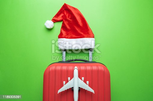 istock Suitcase with Santa hat and airplane model on green background minimal creative Christmas holiday travel concept. 1189305391