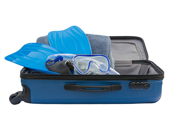 Suitcase with towels, white diving flippers, snorkel and goggles stock photo