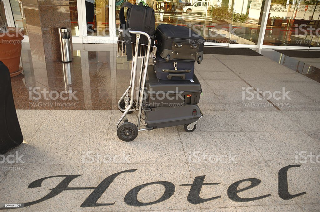 Suitcases and trolley in front of hotel royalty-free stock photo
