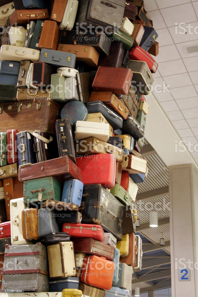 Suitcases stacked dangerously and disorderly in a room royalty-free stock photo
