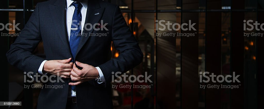 Suited man buttoning jacket stock photo