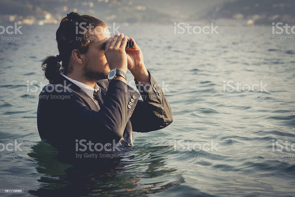 Suited man stood in water looking through binoculars royalty-free stock photo