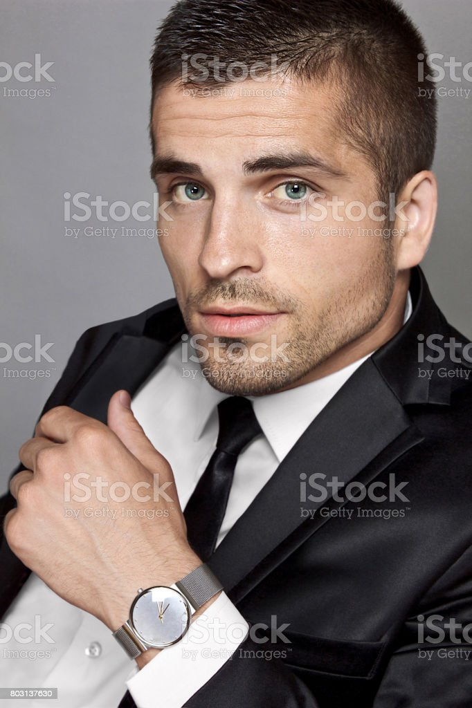 Suited man with wristwatch, portrait stock photo