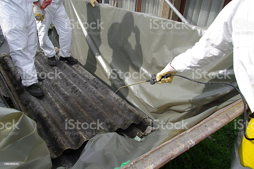 Suited people applying asbestos chemicals stock photo