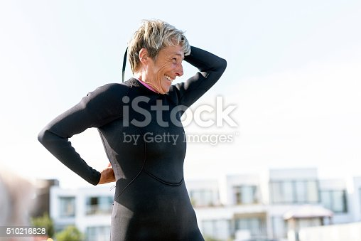 Happy senior woman putting on her wetsuit as she stands at the beach.
