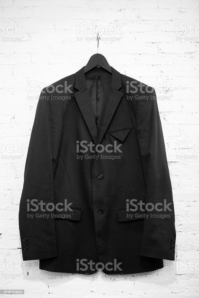 Suits hanging stacked on wall – Foto