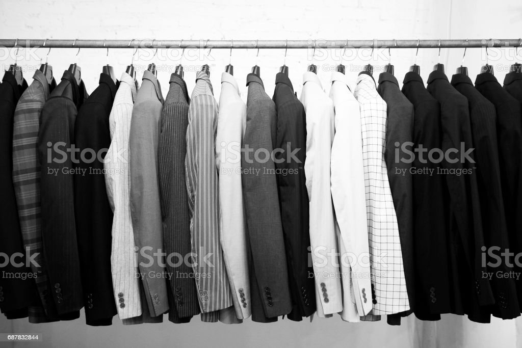 Suits jacket hanging stacked on hanger,black and white stock photo