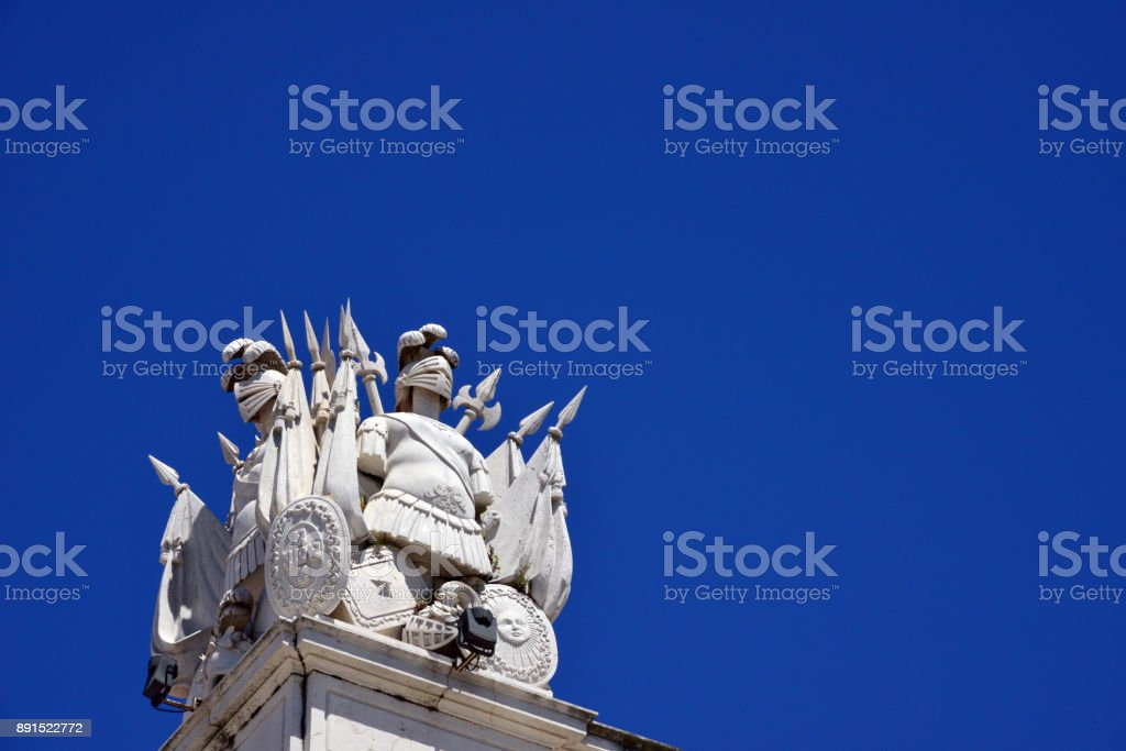 Suits of armor, spears, flags, halberd and shields, 18th century ornaments atop the old Ministry of the Army building, Terreiro do Paço square / Praça do Comércio, Lisbon, Portugal stock photo