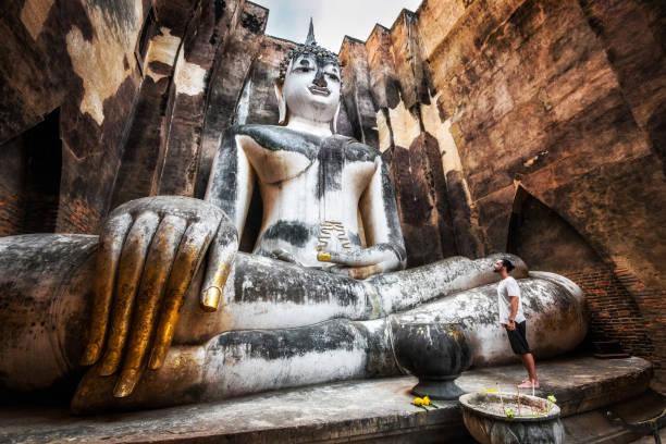 sukhothai parque histórico, tailândia, viajante com buda antiga estátua no templo de wat si chum - sukhothai - fotografias e filmes do acervo
