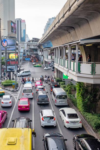 sukhumvit road in bangkok, thailand - motorbike, umbrella stock photos and pictures