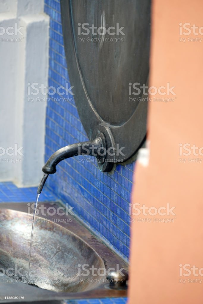 This is a sulfur Drinking water fountain with flowing water in a...