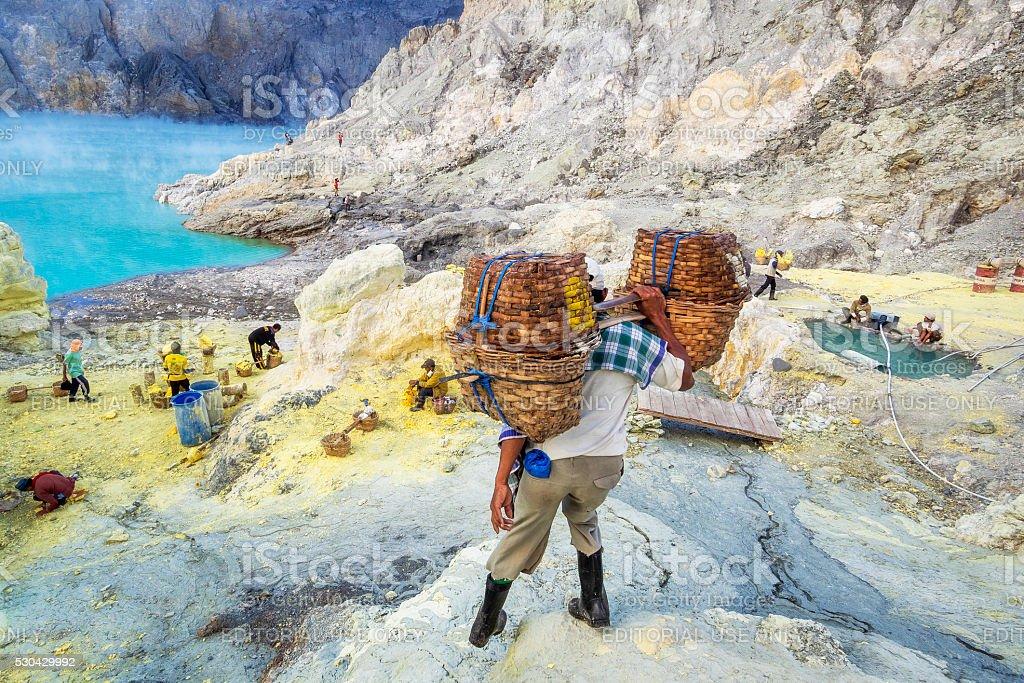 Sulfur Miner Hiking Into Crater of Ijen Volcano, Java, Indonesia stock photo