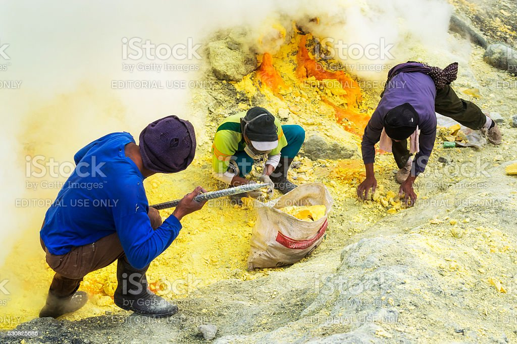 Sulfur Miners at Work, Kawah Ijen Volcano, East Java, Indonesia. stock photo