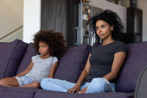 Sulky african child and mother sitting on sofa not talking stock photo
