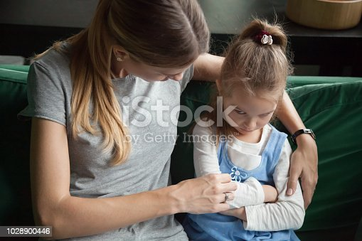 istock Sulky angry offended kid girl pouting ignoring mother scolding her 1028900446