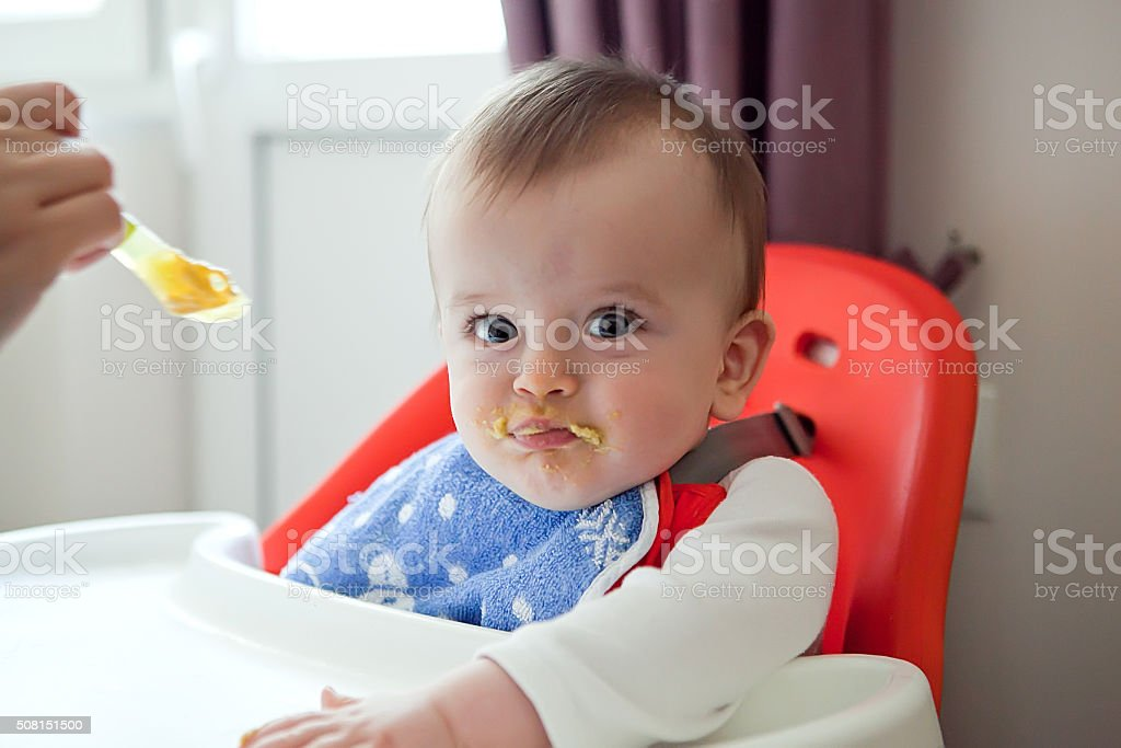 sulky smeared baby refuses to eat a meal stock photo
