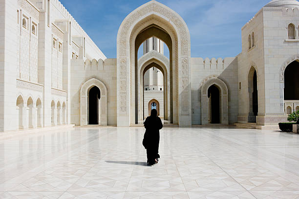 Sultan Qaboos Grand Mosque Muscat Oman Woman in black Abaya Gown walking towards the giant arch in the famous Sultan Qaboos Grand Mosque in Muscat, Oman, Middle East, Arabia. grand mosque stock pictures, royalty-free photos & images