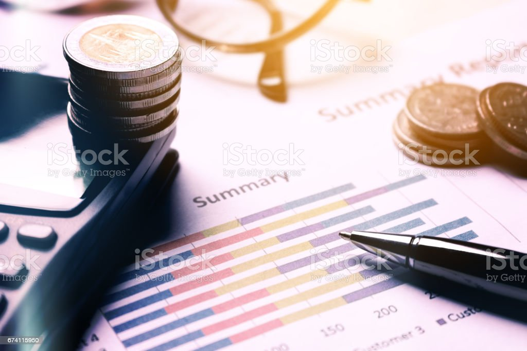 Summary report and business equipment on desk with finance saving concept. royalty-free stock photo