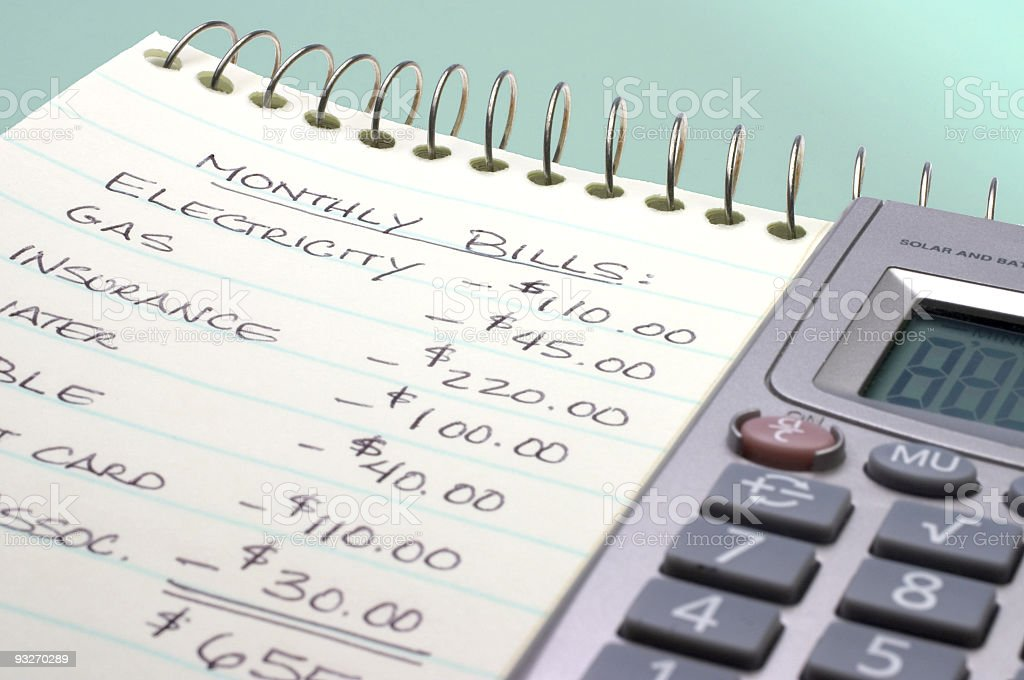 Summation of monthly bills on a notepad by a calculator royalty-free stock photo