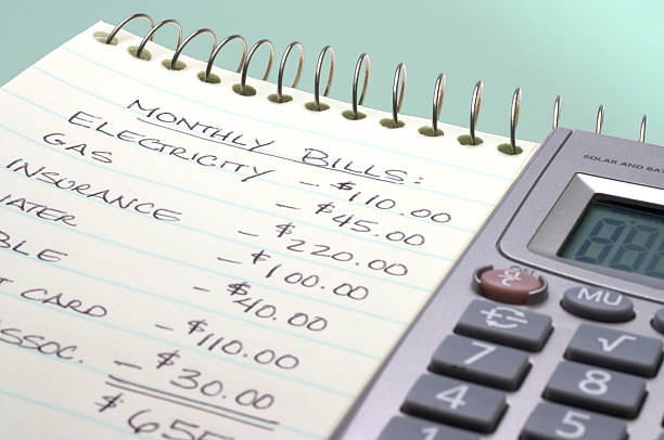summation of monthly bills on a notepad by a calculator - list stock photos and pictures