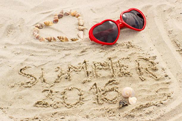 sommer 2016 gezeichnet auf dem sand und herzen von muscheln, sonnenbrille - modefarben sommer 2016 stock-fotos und bilder