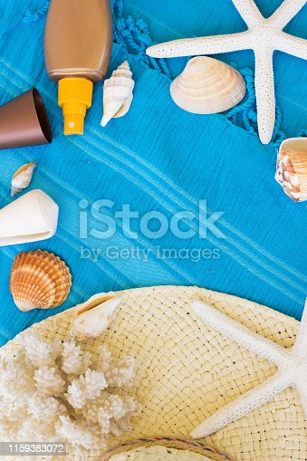 674650538istockphoto Summer Accessories Background. Top View of Summer Beach Accessories. Beach Hat, Sea Shells, Star Fish, Tanning Cream and Sunglasses on a Turquoise Blue Beach Towel. Tropical Summer Concept, Beach Background, Vacation and Travel Concept. 1159383072