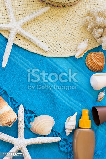 674650538istockphoto Summer Accessories Background. Top View of Summer Beach Accessories. Beach Hat, Sea Shells, Star Fish, Tanning Cream and Sunglasses on a Turquoise Blue Beach Towel. Tropical Summer Concept, Beach Background, Vacation and Travel Concept. 1159383077