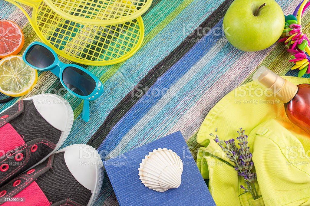 Summer accessories on beach towel top view