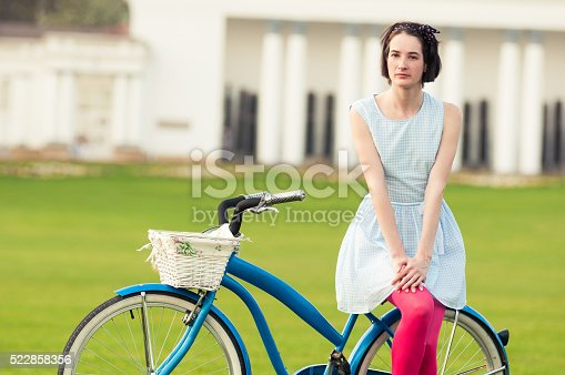 Summer activity concept with attractive woman standing on vintage bicycle outside