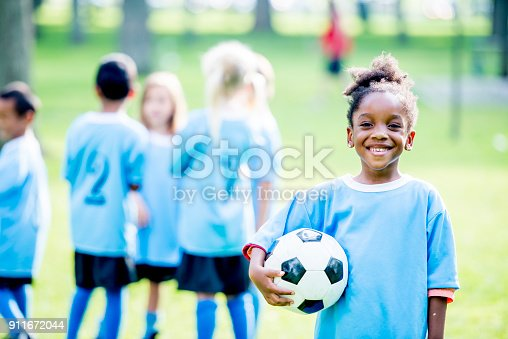 A group of kids wearing soccer uniforms are outdoors on a summer day. A girl of African descent in the foreground is smiling at the camera while holding