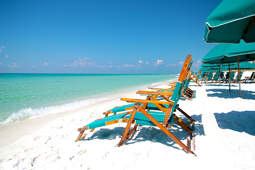 Sunny Adirondak beach chairs with umbrellas in the sand and surf