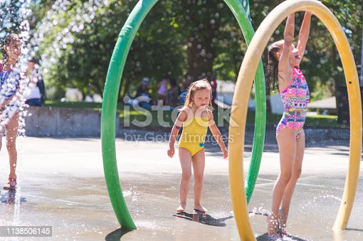 A group of young children frolic and run in a playground splash pad. It is a sunny, perfect day for getting wet and playing hard! Three young girls in swimsuits are running through the sprinklers and yelling and laughing as the water droplets cascade around.