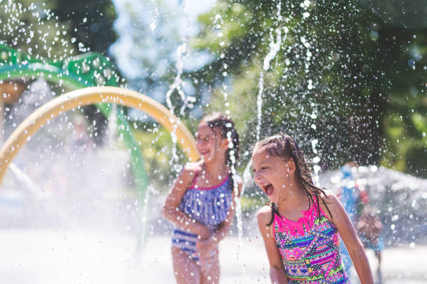 summer afternoon at the splash pad - children play water park stock photos and pictures