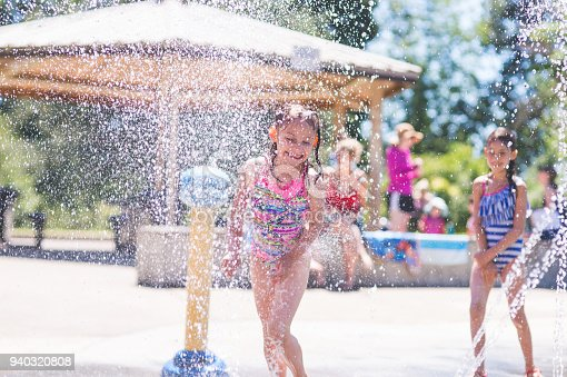 A group of young children frolic and run in a playground splash pad. It is a sunny, perfect day for getting wet and playing hard! A young girl in a swimsuit is running through the sprinklers and yelling and laughing as the water droplets cascade all around and her friends wait in the background.