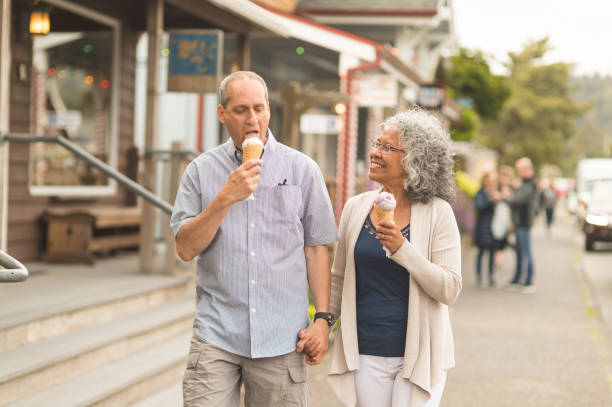 A summer afternoon together... A senior couple enjoy a walk together and ice cream cones on a lovely summer afternoon. They are passing by several small businesses in a small downtown district. She is looking at him with love...or maybe looking at his ice cream. americana stock pictures, royalty-free photos & images