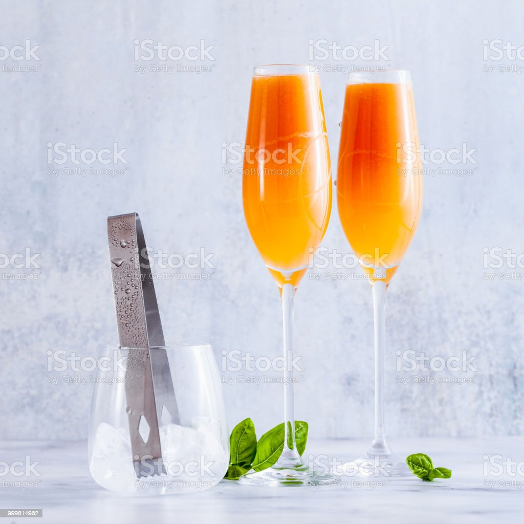 summer alcoholic fruit drink in glasses for champagne. on the marble table. with ice. refreshing cocktail stock photo
