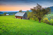 Magical rural farm with old wooden hut and stunning sunset near Bran, Transylvania, Romania ,Europe