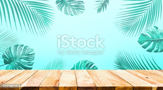 Summer and nature product display with wood table counter on palm leaf in vibrant color background.For key visual layout