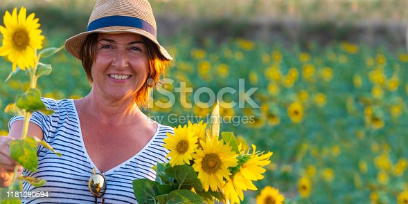 Mid age cute woman with a hat, smiling in sunflower field at sunset.