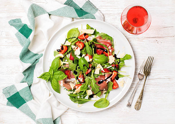 summer arugula, prosciutto, strawberry salad with glass of rose wine - balsamico stockfoto's en -beelden