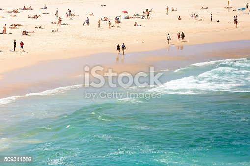 Summer at the beach and ocean, Bondi Beach is crowded with a large number of beachgoers on a hot Sunday afternoon, full frame horizontal composition with copy space