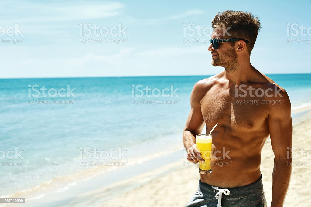 Summer. Athletic Muscular Man Drinking Juice Cocktail On Beach stock photo