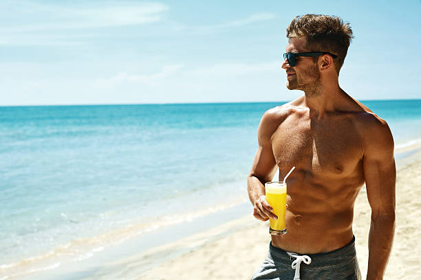 summer. athletic muscular man drinking juice cocktail on beach - sexe symbole photos et images de collection