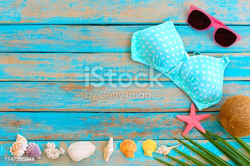 699960484istockphoto Summer background with bikini, sunglasses, coconut, starfish, coral and shells on blue wooden background. 1147285944