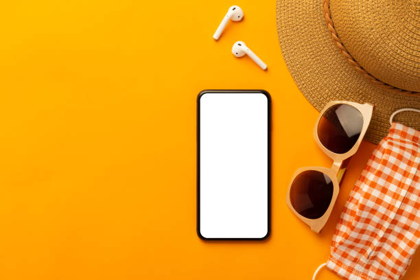 summer background with blank screen phone and beach accessories, mask to prevent covid-19 on vibrant orange background top view with copy space - phone, travelling, copy space imagens e fotografias de stock