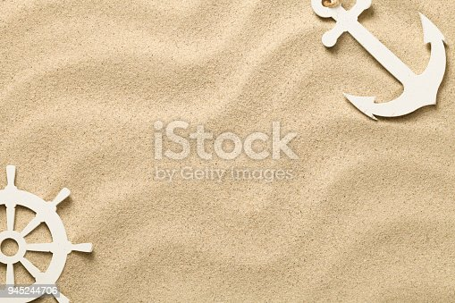 istock Summer Background with Decorative Anchor and Ship steering Wheel 945244706