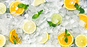 Summer background with fresh and juicy citrus fruits on ice background, panorama