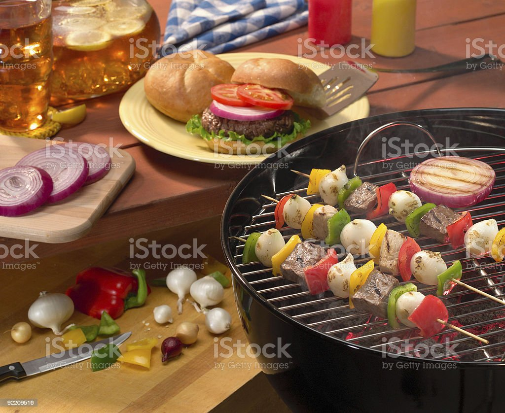 Summer backyard BBQ with burgers & kabobs royalty-free stock photo